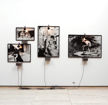 1200 Christian Boltanski, Dog in the street, Children Playing, Bathtime, Toys (intstalltion view), 1991. Gelatin silver photograph, biscuit box, lamp and electrical wires. Dimensions variable. 1