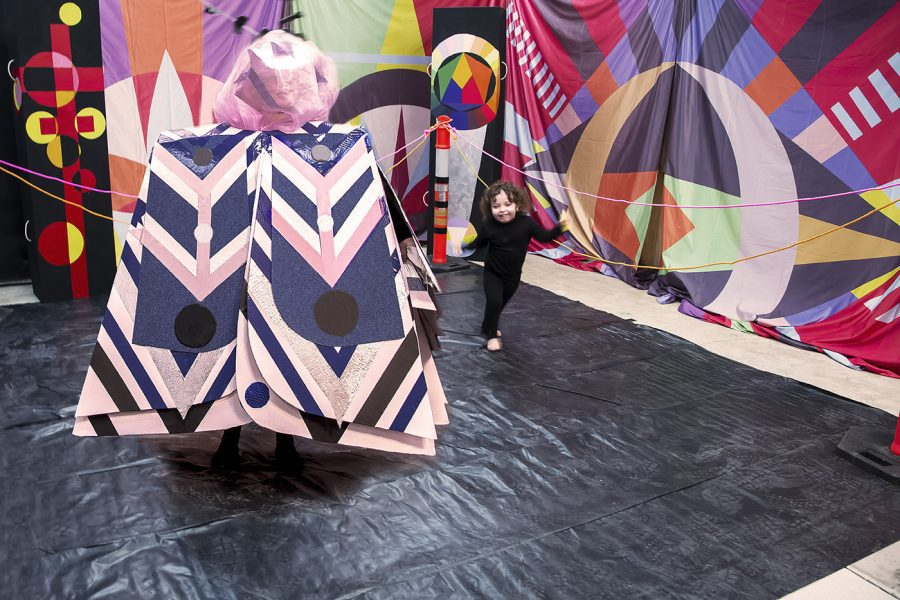 Costumed performer and toddler inside a colourful installation.